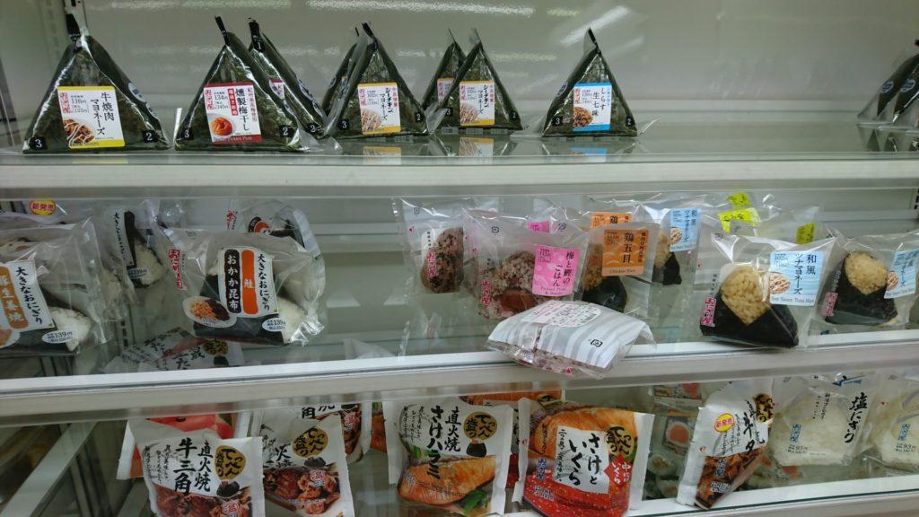 Olika typer av onigiris till försäljning i en convenience store