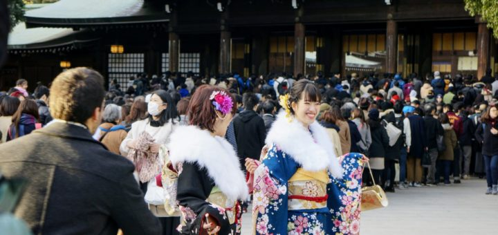 Unga damer i kimono som firar vid templet